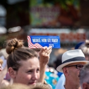 "Iowan holds ""Make Him Go Away for 2020"" sign at state fair during Democratic presidential candidates visit."