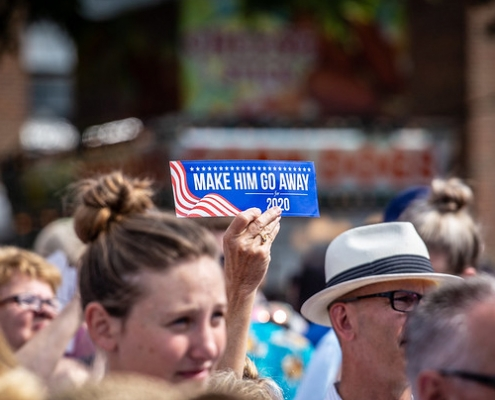 """Iowan holds """"Make Him Go Away for 2020"""" sign at state fair during Democratic presidential candidates visit."""