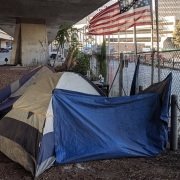 Homeless tents and flag under CA-87 in San Jose