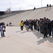 Immigrants lined up at a border area.