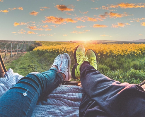 Young couple watching sunset in rural environment.